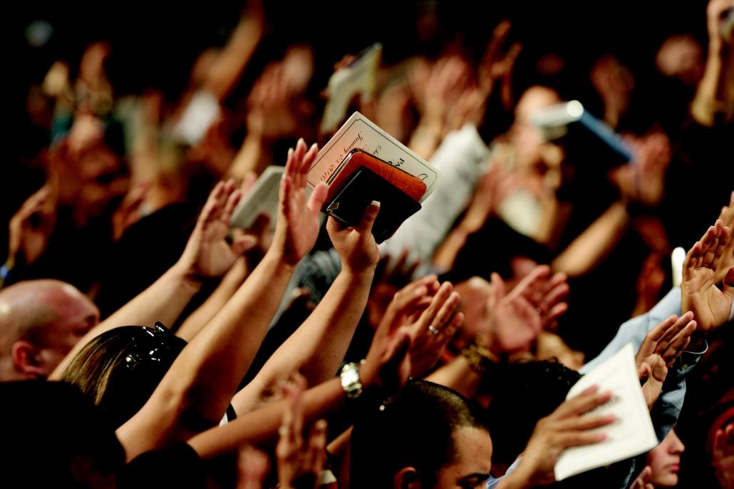 Betende Menschen strecken die Hände in die Höhe