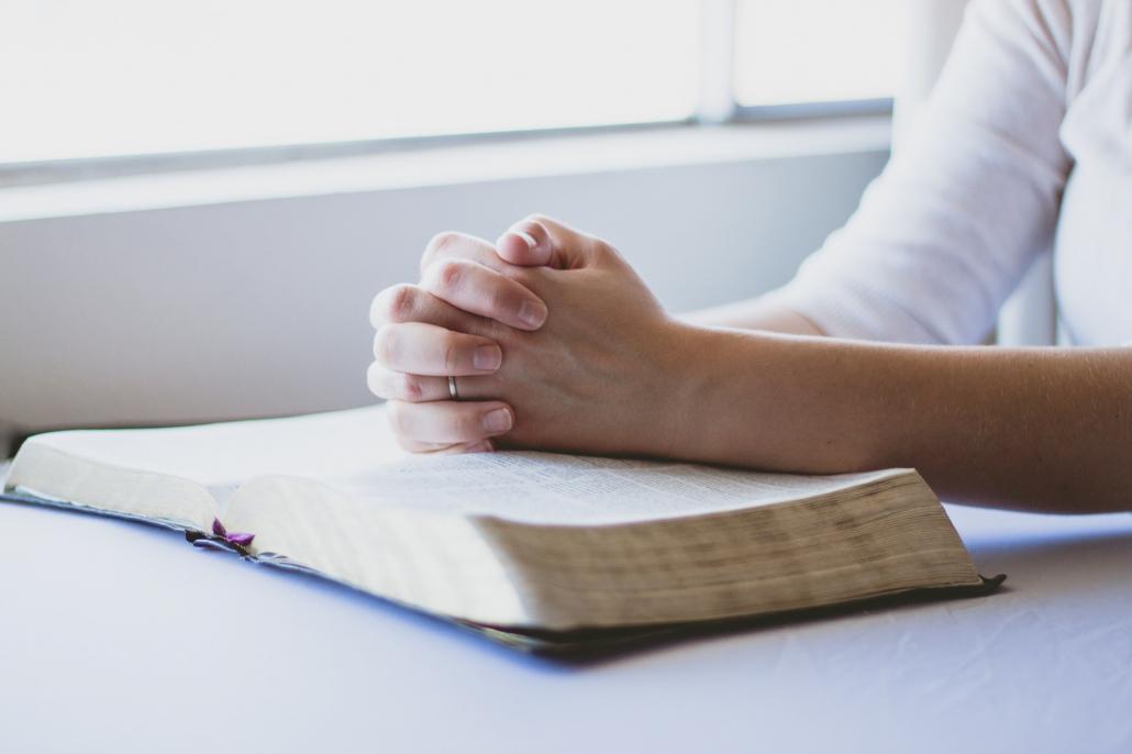 Betende Hände auf einer Bibel